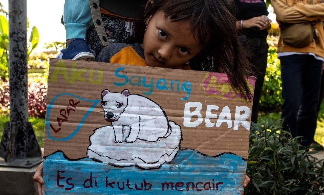 Criança indonésia exibe cartaz com um urso polar faminto à deriva em um iceberg derretendo enquanto se junta a um comício como parte de uma campanha global de mudança climática Foto: JUNI KRISWANTO / AFP
