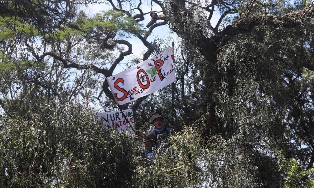 Um garoto segura uma bandeira sentado em uma árvore durante um protesto pedindo ação contra as mudanças climáticas, em Nairóbi, capital do Quênia, África Foto: SIMON MAINA / AFP