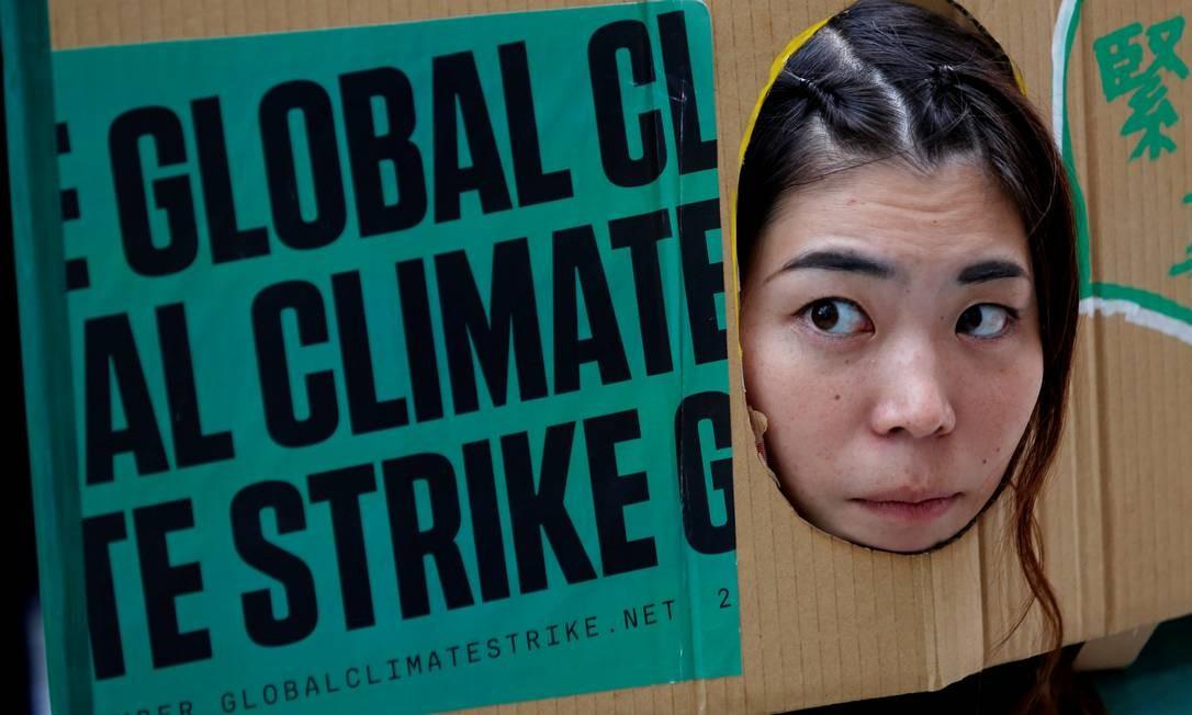 Uma mulher coloca no cartaz de protesto em Tóquio evento para marcar o dia das greves climáticas globais em Tóquio, Japão Foto: KIM KYUNG-HOON / REUTERS