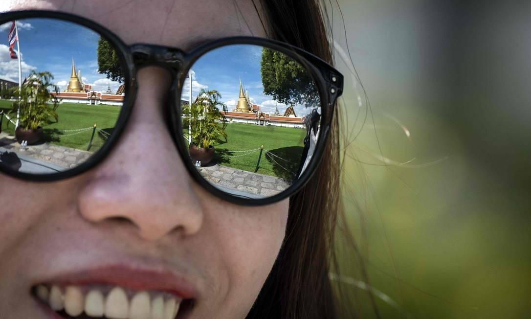 O Grande Palácio Real, refletido nos óculos da visitante, é uma das principais atrações de Bangcoc, na Tailândia Foto: MLADEN ANTONOV / AFP
