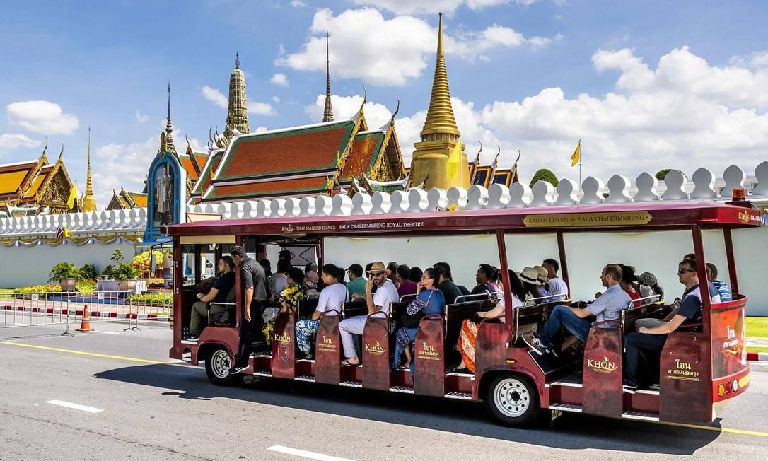Um ônibus turístico para em frente ao Grande Palácio Real, que fica no coração da capital tailandesa Foto: MLADEN ANTONOV / AFP