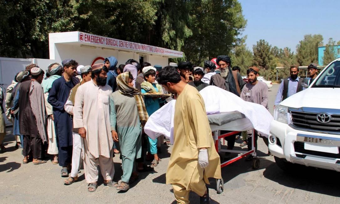 Homens carregam um dos corpos resgatados após ataques realizados por forças afegãs Foto: NOOR MOHAMMAD / AFP
