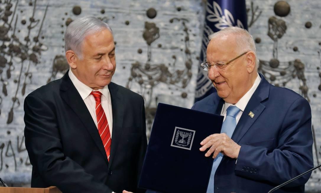 Benjamin Netanyahu (esq.), há dez anos premier de Israel, recebe do presidente Reuven Rivlin (dir.) a tarefa de formar um novo gabinete. Pouco depois, defendeu um governo de união nacional Foto: MENAHEM KAHANA / AFP