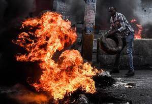 Manifestante protesta com pneus em chamas contra a escassez de combustível e para exigir a renúncia do presidente Jovenel Moise, em Porto Príncipe Foto: CHANDAN KHANNA / AFP