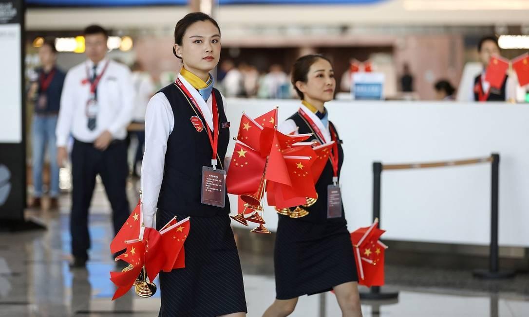 Funcionárias do aeroporto durante os preparativos para a cerimônia de inauguração Foto: STR / AFP