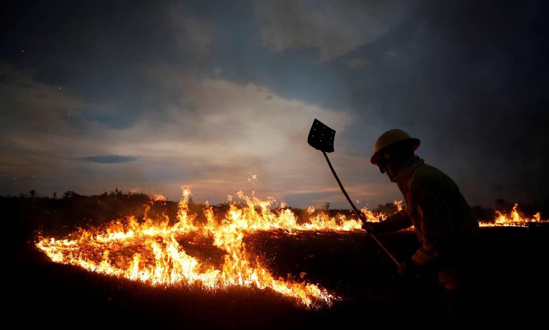 Agente da brigada anti-incêndio do Ibama tenta conter chamas na terra indígena Tenharim Marmelos, no Amazonas Foto: BRUNO KELLY / REUTERS