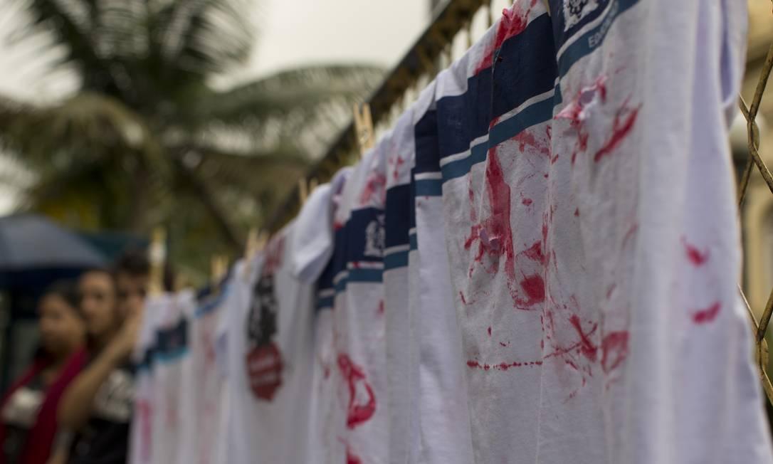Manifestantes instalaram um varal na fachada do prédio e penduraram 16 uniformes escolares manchados de vermelho Foto: Márcia Foletto / Agência O Globo