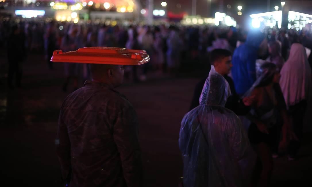 Para quem estava sem capa, valeu o improviso: tampa de lixeira foi usada para se proteger Foto: Pedro Teixeira / Agência O Globo