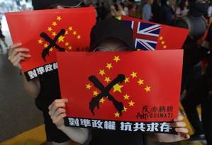 Manifestantes carregam cartazes contra o governo chinês durante protestos em Hong Kong Foto: NICOLAS ASFOURI / AFP / 29-09-2019