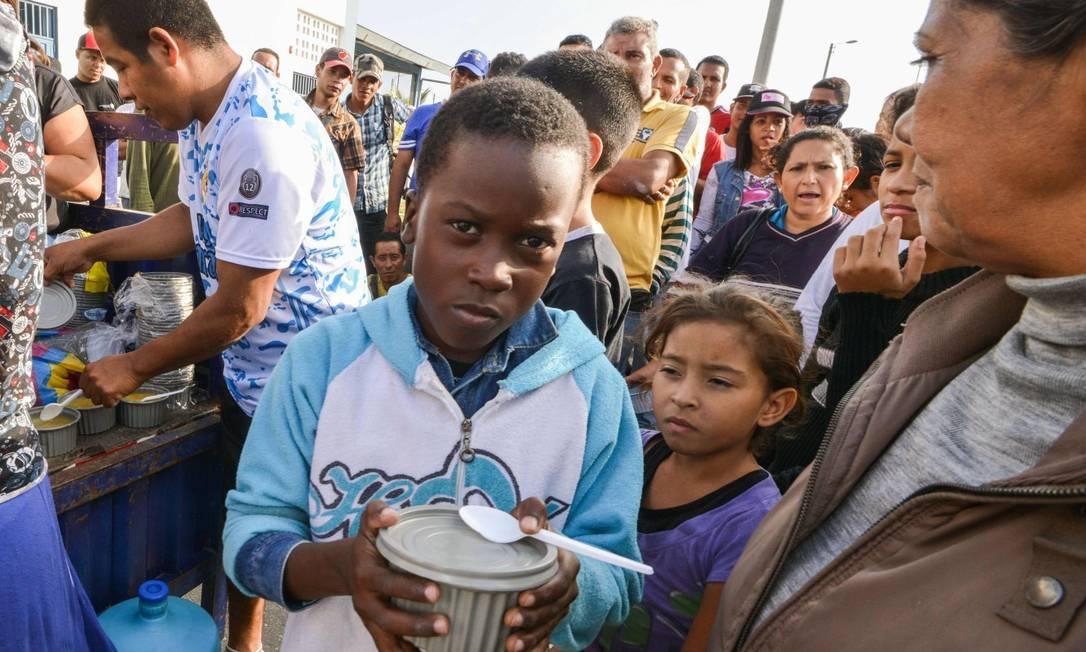 Venezuelanos recebem comida de voluntários enquanto aguardam autorização para entrar no Peru Foto: CRIS BOURONCLE / AFP / 23-08-2018