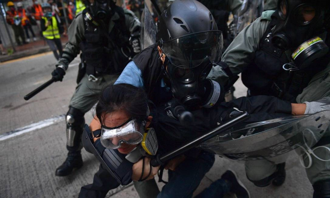 Policiais de Hong Kong agridem um manifestante durante protestos pró-democracia Foto: NICOLAS ASFOURI / AFP