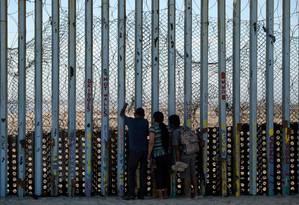 Pessoas olham através da barreira na fronteira entre os EUA e o México em Tijuana Foto: GUILLERMO ARIAS / AFP/14-9-2019