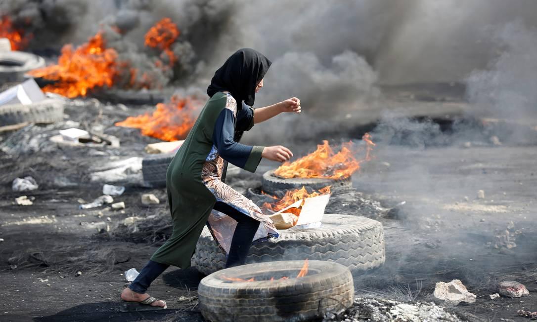 Uma manifestante corre entre pneus queimados durante um toque de recolher, dois dias após protestos contra o governo que se tornarem violentos em Bagdá Foto: WISSM AL-OKILI / REUTERS