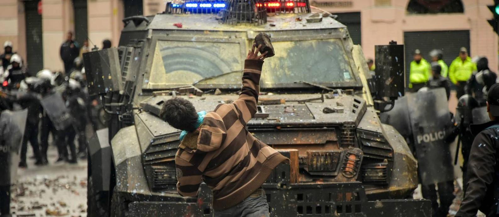Em Quito, manifestante atira pedra contra blindado das forças de segurança do Equador em protesto contra a política econômica e a alta dos combustíveis Foto: RODRIGO BUENDIA / AFP