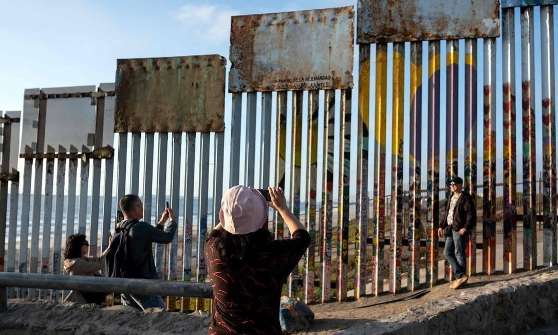 Visitantes fotografam o trecho da cerca que separa México e Estados Unidos, na altura da fronteira em Tijuana Foto: GUILLERMO ARIAS / AFP