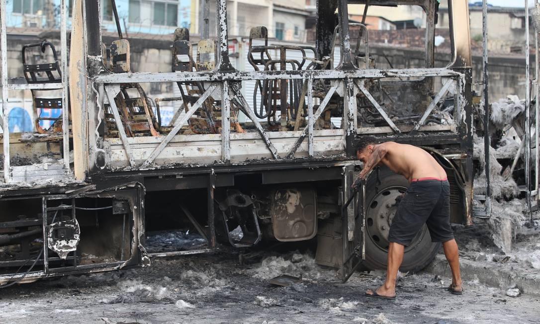 Homem retira peças da carcaça do ônibus Foto: Fabiano Rocha / Agência O Globo