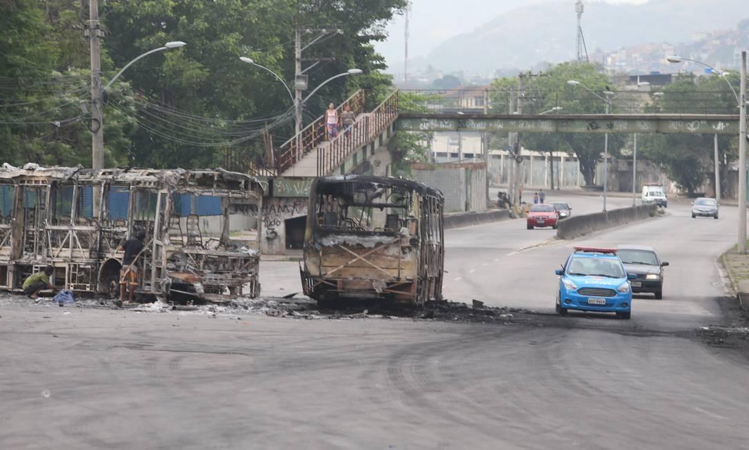 As carcaças dos ônibus incendiados continuavam nas vias da região na manhã desta sexta Foto: Fabiano Rocha / Agência O Globo