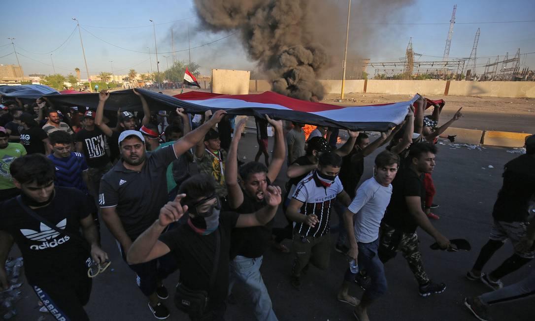 Manifestantes carregam bandeira do Iraque durante protesto nesta sexta na capital Bagdá: ao menos 65 pessoas foram mortas nas manifestações dos últimos três dias no país Foto: AHMAD AL-RUBAYE/AFP