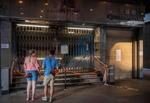 Turistas em frente a uma loja que foi alvo de vandalismo Foto: NICOLAS ASFOURI / AFP