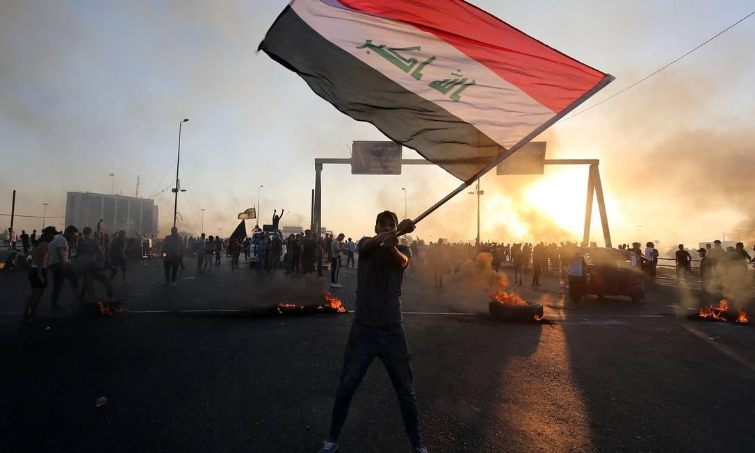 Manifestante agita a bandeira do Iraque no protestos deste sábado: má situação econômica do país e corrupção no governo alimentam insatisfação Foto: AHMAD AL-RUBAYE/AFP
