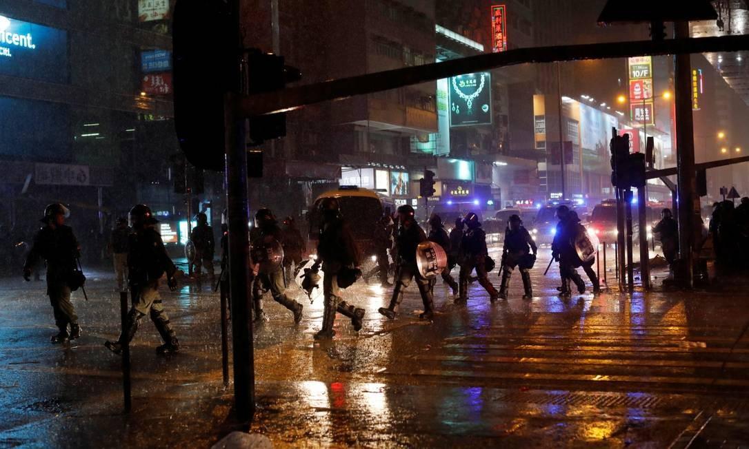 Debaixo de chuva, policiais de Hong Kong tentam conter manifestantes Foto: JORGE SILVA / REUTERS