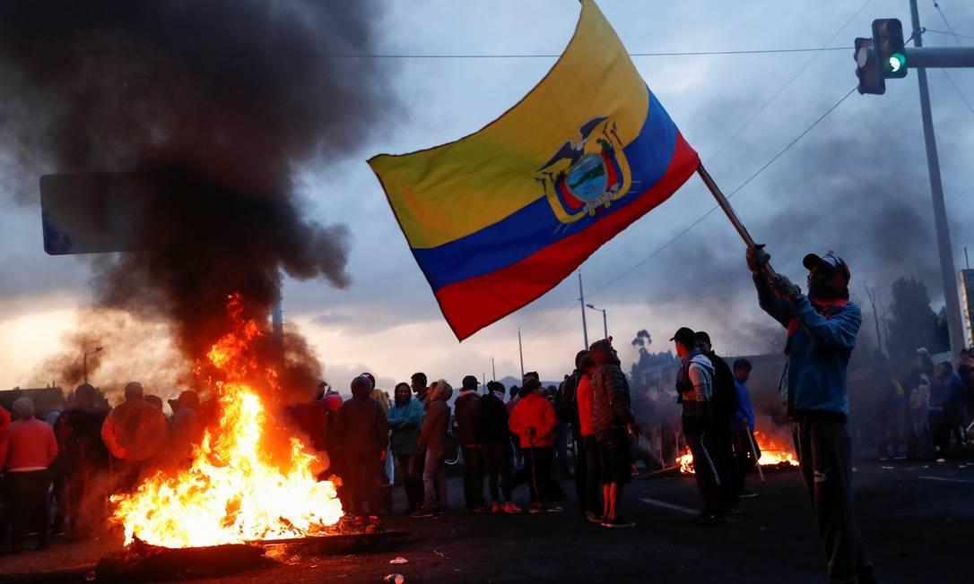 Homem carrega bandeira do Equador ao lado de pessoas que bloqueiam estrada em Lasso, Equador Foto: CARLOS GARCIA RAWLINS / REUTERS