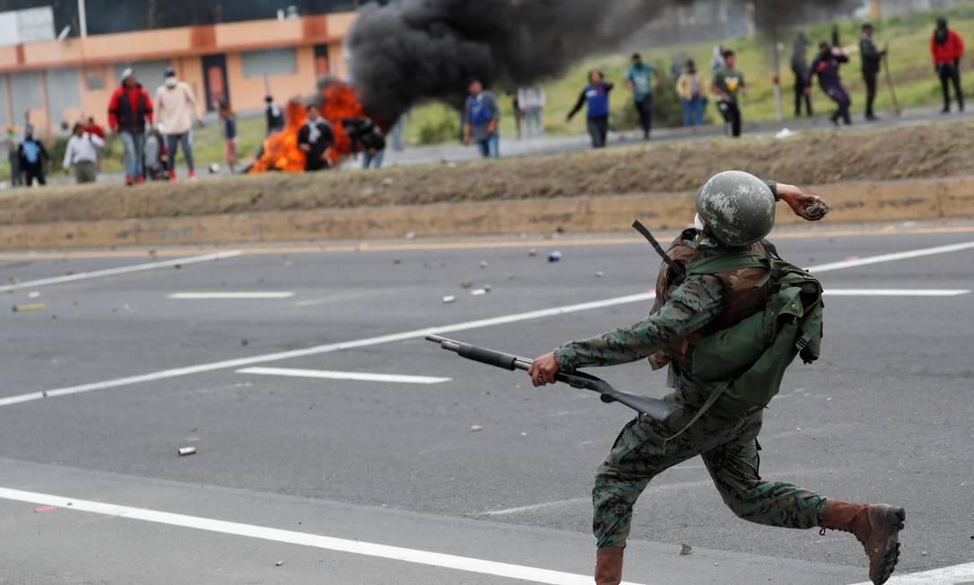 Soldado joga pedra nos manifestantes durante bloqueio a rodovia Foto: CARLOS GARCIA RAWLINS / REUTERS