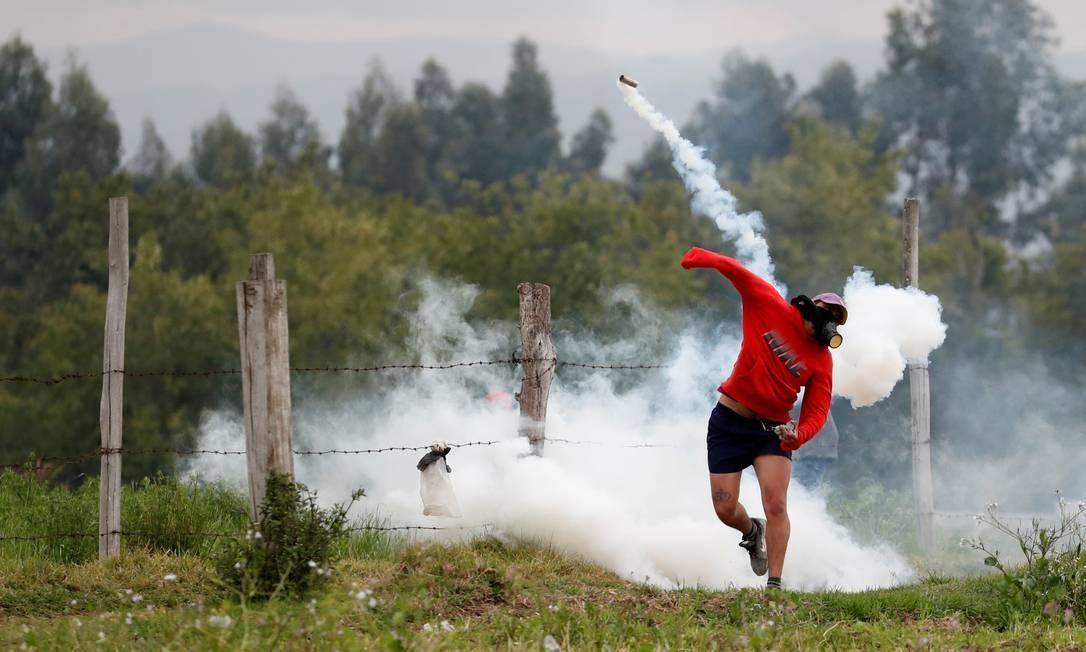 Manifestante arremessa bomba de gás lacrimogêneo disparada pela polícia Foto: CARLOS GARCIA RAWLINS / REUTERS