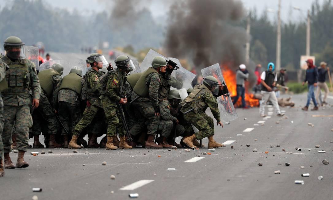 Soldados em formação de combate se protegem de manifestantes Foto: CARLOS GARCIA RAWLINS / REUTERS