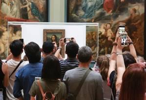 Visitantes fotografam a Mona Lisa na Galeria Medici, no Museu do Louvre, em agosto de 2019 Foto: OWEN FRANKEN / NYT