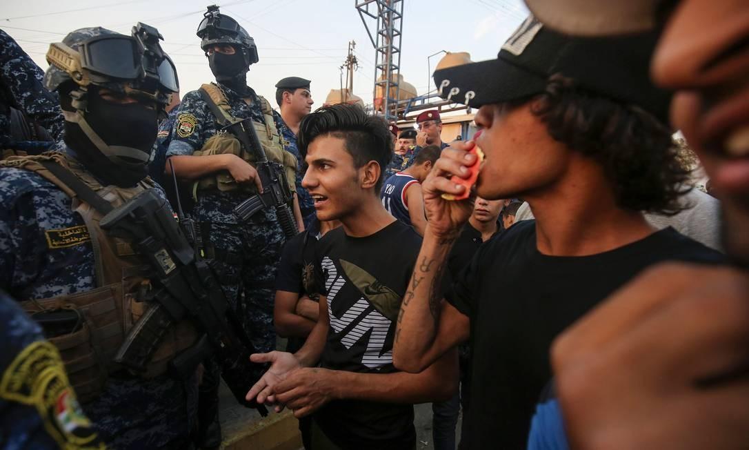 Manofestantes conversam com integrantes das forças de segurança iraquianas no volátil distrito de Sadr City, em Bagdá: militares prometeram investigar uso excessivo de força na repressão à onda de protestos Foto: AHMAD AL-RUBAYE/AFP