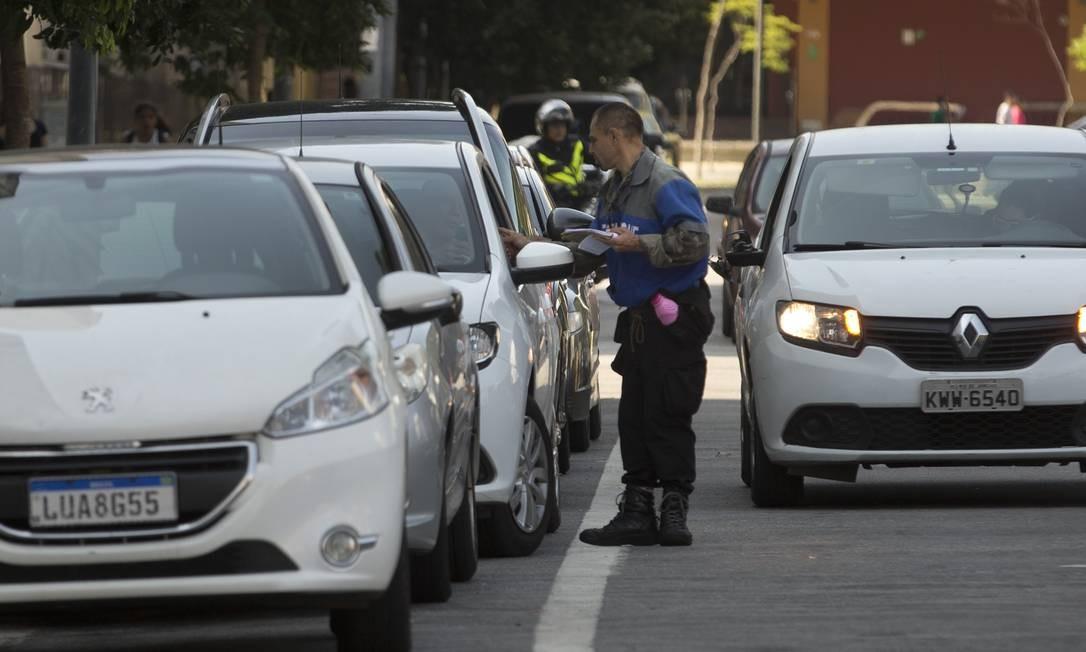 Flanelinha cobra R$ 10 para estacionar na rua Edgard Gordilho, na Zona Portuária, e dá um RPA como recibo Foto: Márcia Foletto / Agência O Globo