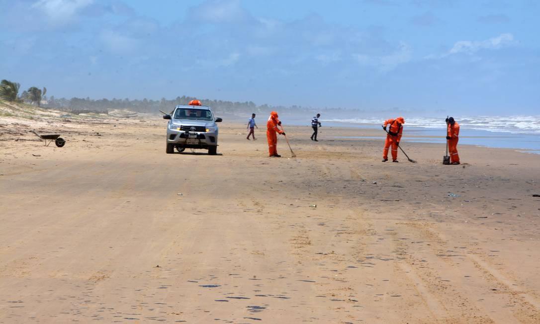Técnicos trabalham na retirada de manchas de patróleo nas proximidades da Praia do Viral, em Aracaju Foto: Márcio Garcez / Agência O Globo