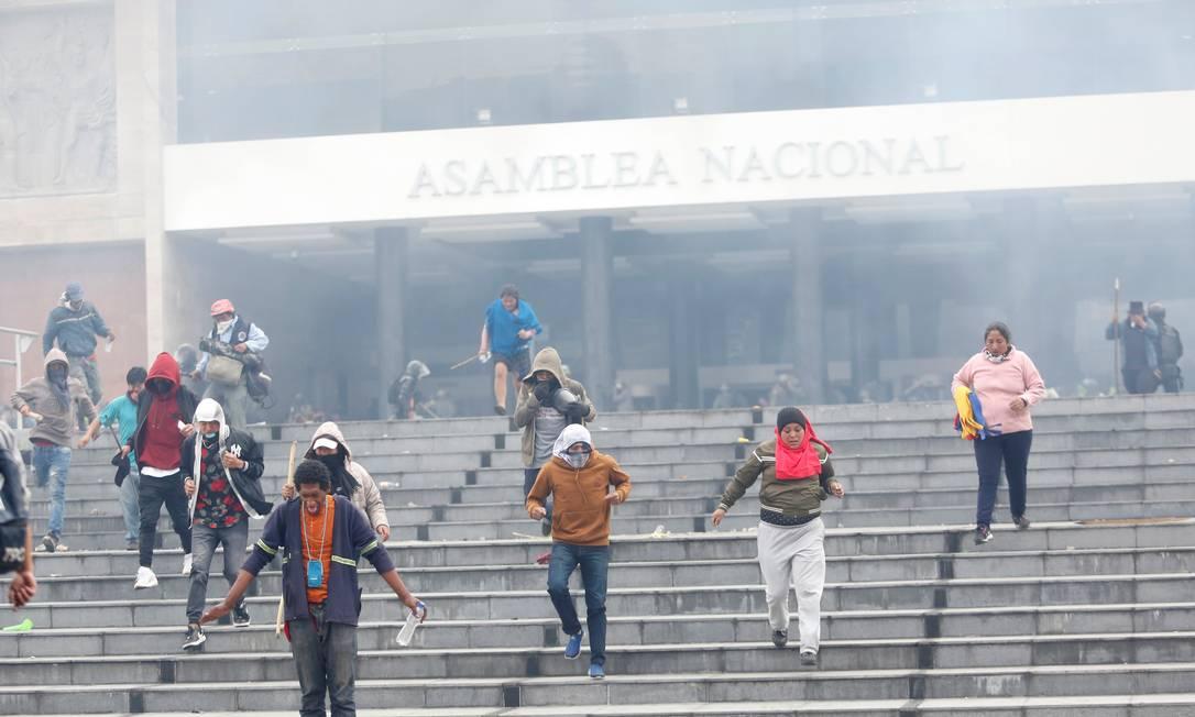 Manifestantes deixam a Assembleia do Equador após serem expulsos pela polícia. Governo decretou toque de recolher em áreas próximas a edifícios públicos Foto: DANIEL TAPIA / REUTERS