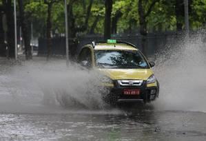 Táxi trafega por via alagada perto da Praça Paris, no Centro Foto: Fabiano Rocha / Agência O Globo
