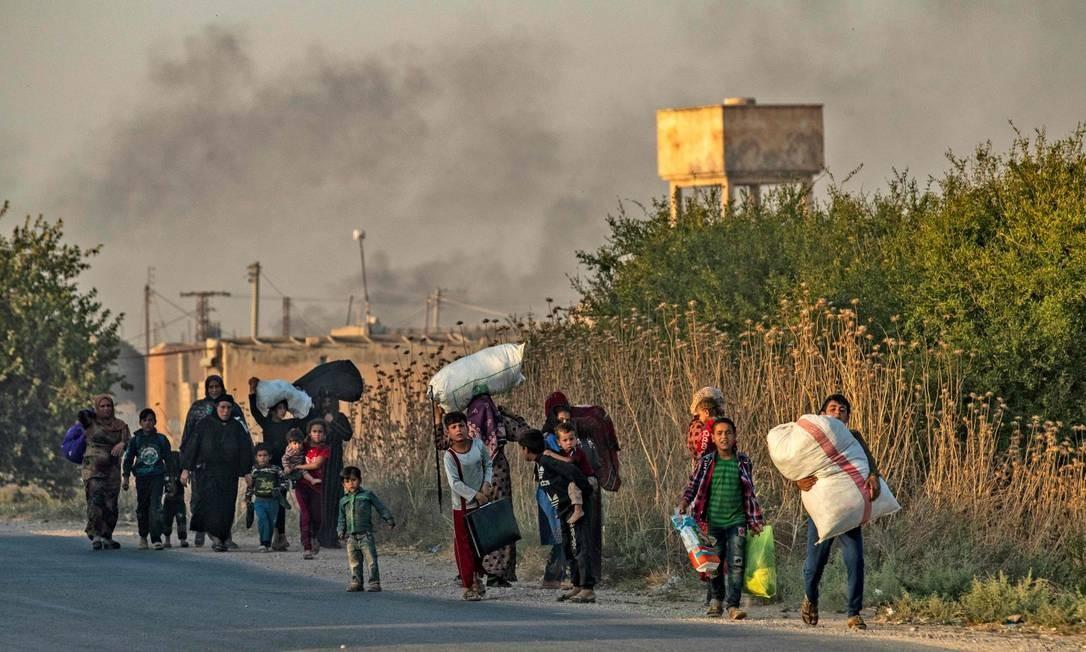 Civis fogem de bombardeios turcos na cidade de Ras al-Ain, no nordeste da Síria Foto: DELIL SOULEIMAN / AFP