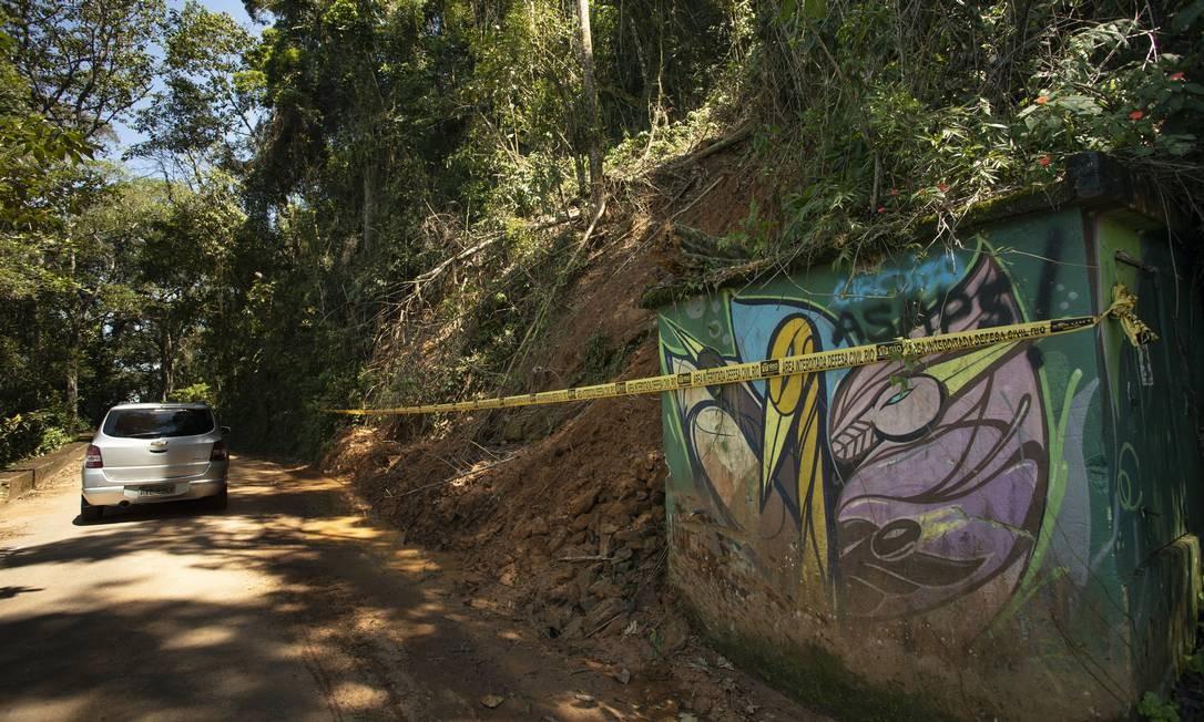 """Carro circula na Estrada do Sumaré, na localidade conhecida como """"Caixa D'Água"""", que está com barranco e faixa da Defesa Civil Foto: Ana Branco / Agência O Globo"""