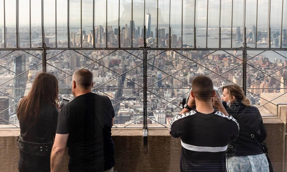 Visitantes fotografam a partir do mirante no 86º andar do Empire State Building, em Nova York Foto: Mark Wickens / The New York Times