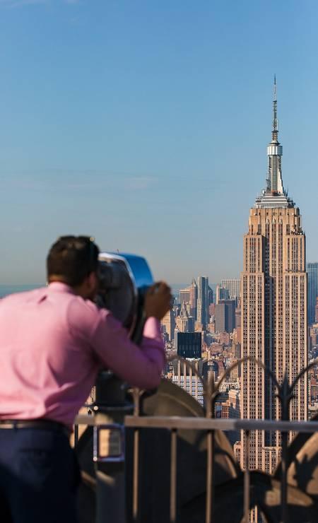 Homem observa o Empire State Building a partir do mirante do Rockefeller Center, em Nova York Foto: Mark Wickens / The New York Times