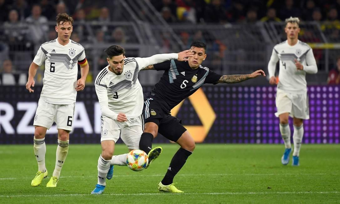 O alemão Serdar, à esquerda, disputa a bola com o argentino Leandro Paredes Foto: INA FASSBENDER / AFP