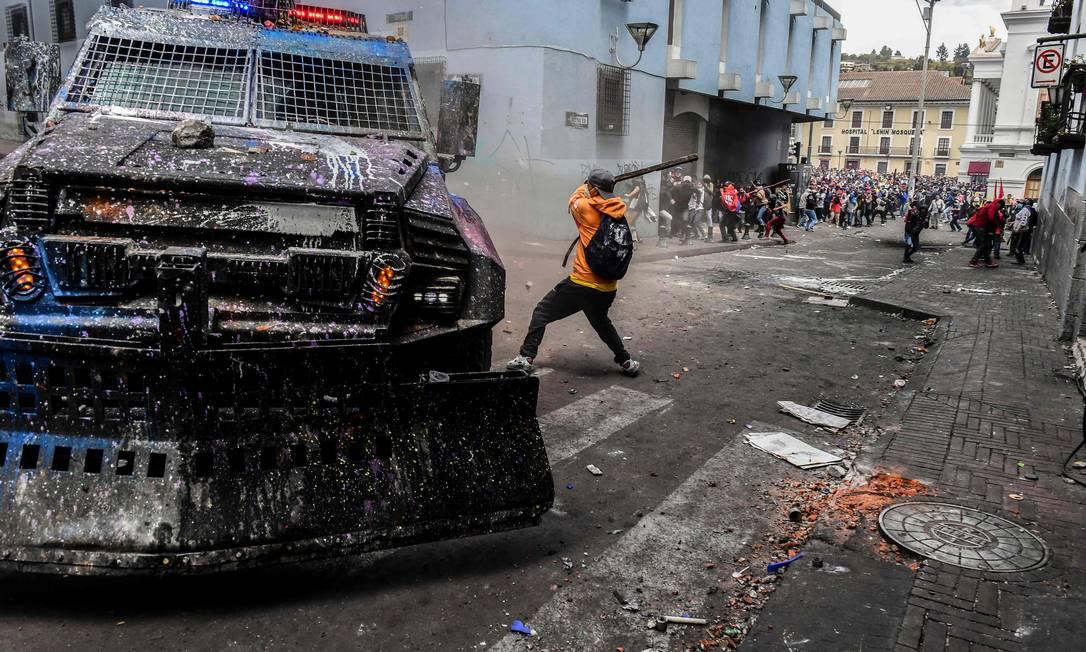 Manifestante atinge um veículo blindado durante confrontos com a polícia em Quito Foto: MARTIN BERNETTI / AFP