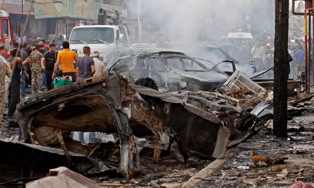Socorristas e curiosos se aglomeram no local do ataque do Estado Islâmico na cidade síria de Qamishli, controlada pelos curdos, nesta sexta: explosão de carro-bomba deixou ao menos três mortos e nove feridos Foto: MOHAMMED AHMAD/AFP
