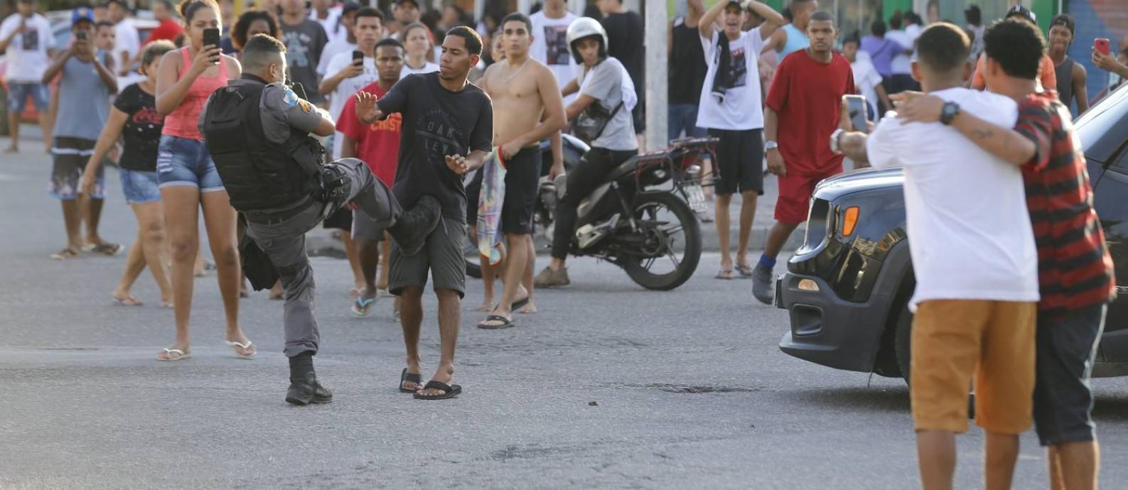 PM agride homem durante protesto após enterro do jovem Kelvin, de 17 anos, morto nesta quinta-feira durante ação na comunidade Pára-Pedro Foto: MARCELO THEOBALD / Agência O GLOBO