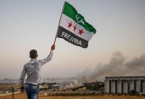 Homem segura bandeira da oposição Síria que diz 'Síria Livre' enquanto cidade da fronteira é atacada por forças turcas Foto: BULENT KILIC / AFP