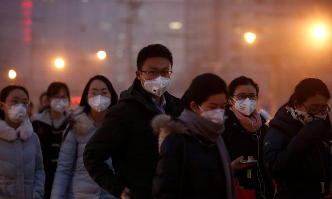 População caminha nas ruas de Pequim com máscaras contra poluição, em registro de 2017 Foto: Thomas Peter / Reuters