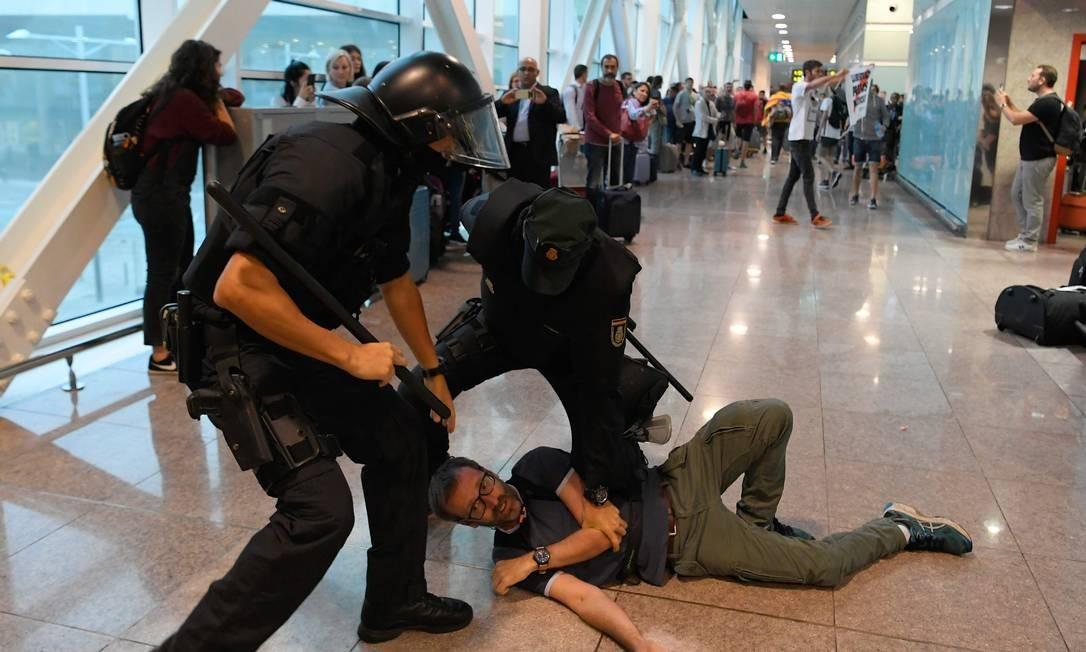 Policiais espanhóis prendem manifestante no Aeroporto El Prat, em Barcelona Foto: LLUIS GENE / AFP