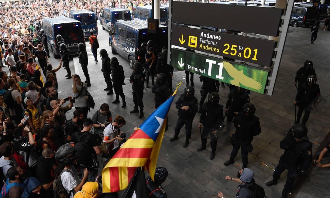 Policiais fazem uma barreira do lado de fora do aeroporto para impedir a entrada de manifestantes Foto: JOSEP LAGO / AFP