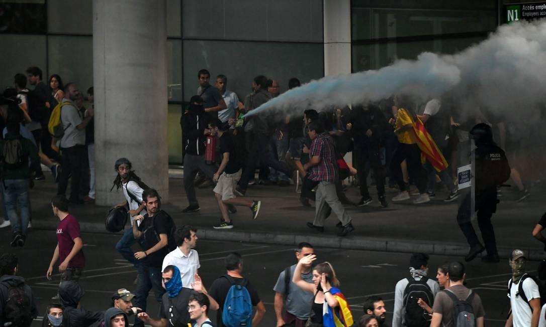 Manifestantes descarregam extintores de iincêndio nos policiiais no Aeroporto El Prat, em Barcelona Foto: LLUIS GENE / AFP
