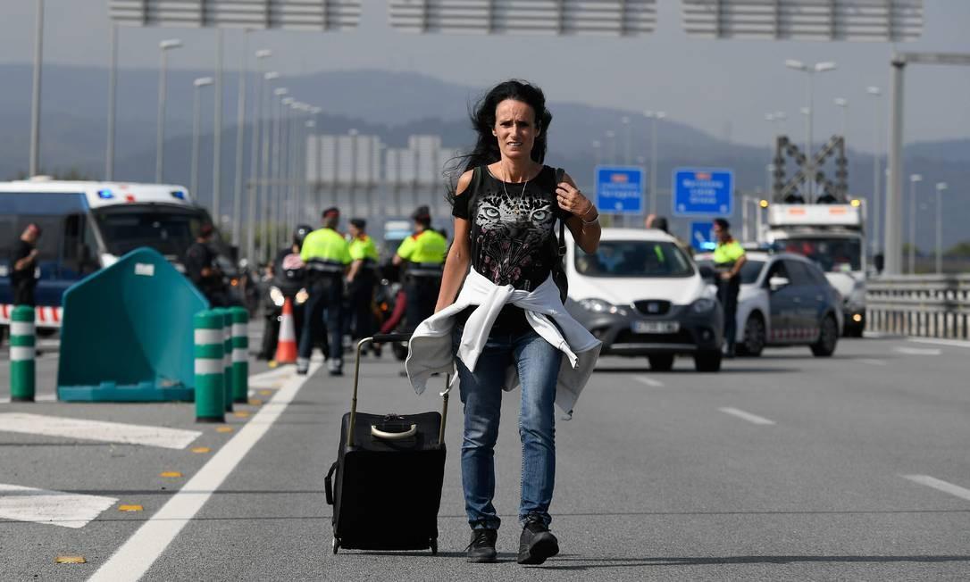 Em razão do protesto, acessos ao Aeroporto El Prat fiicaram congestionados, obrigando quem tinha viagem marcada a caminhar até o o terminal aeroviário Foto: LLUIS GENE / AFP