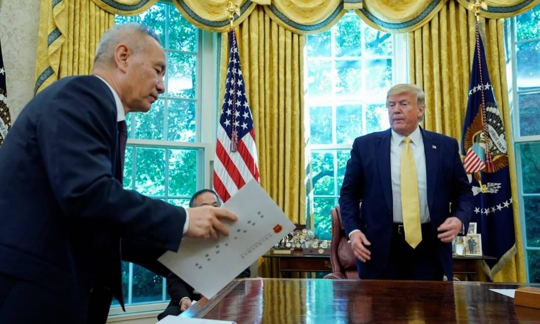 O presidente dos EUA, Donald Trump, e o vice-primeiro-ministro chinês Liu He no Salão Oval da Casa Branca, após assinarem um acordo parcial Foto: Reuters